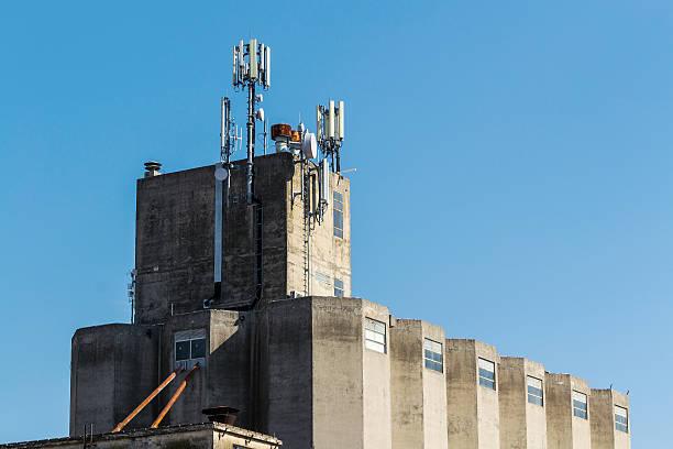 stabilimento industriale con gsm antenne sul tetto - emissione radio televisiva foto e immagini stock