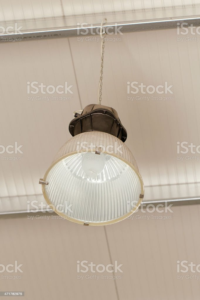 Industrial ceiling lamp hanging from the roof royalty-free stock photo