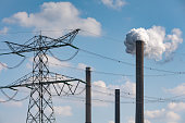 istock industrial chimney polluting the environment next to an electricty pylon 1192467467