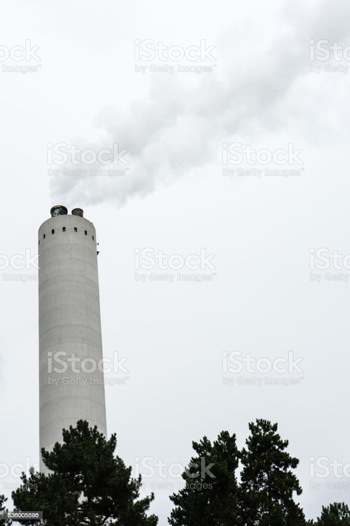 industrial chimney with smoke with tree in the front stock photo