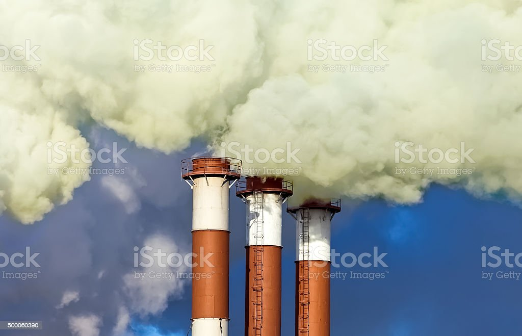 Industrial chimneys with smoke over blue sky stock photo