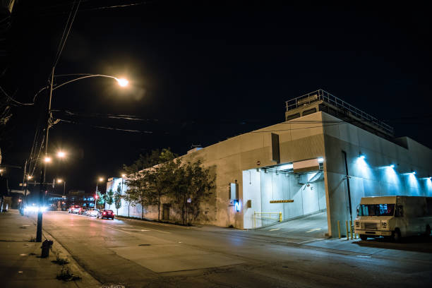 Industrial city warehouse with truck and urban street traffic at night. stock photo