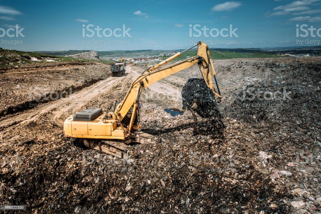 Industrial city waste dump yard details - excavator doing construction works stock photo