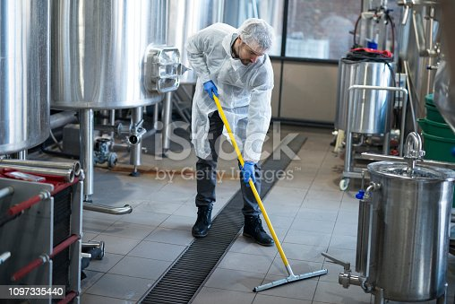 Industrial cleaning service. Professional cleaner wearing protection uniform cleaning floor of production plant.