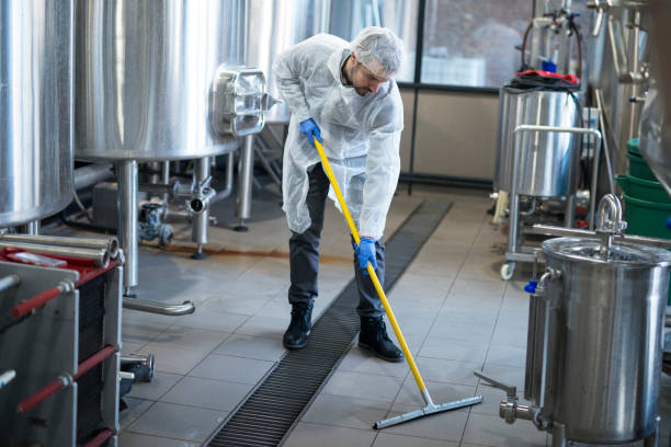 industrial cleaning service. professional cleaner wearing protection uniform cleaning floor of production plant. - magazyn miejsce pracy zdjęcia i obrazy z banku zdjęć
