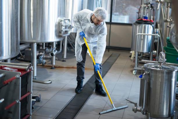 industrielle reinigungs-service. professionelle reiniger verschleißschutz einheitliche bodenreinigung produktionsanlage. - hausmeister stock-fotos und bilder