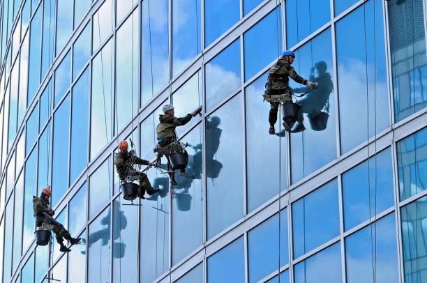 Industrial climbers wash windows of skyscraper stock photo