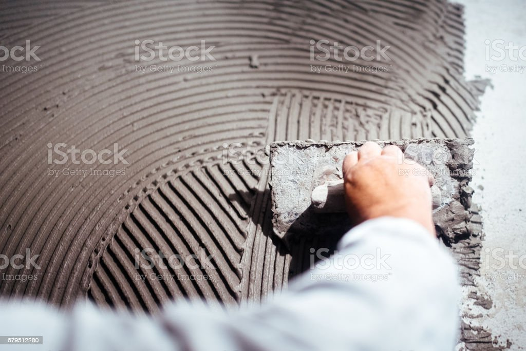 industrial close up of worker hand adding adhesive for ceramic tiles installation stock photo