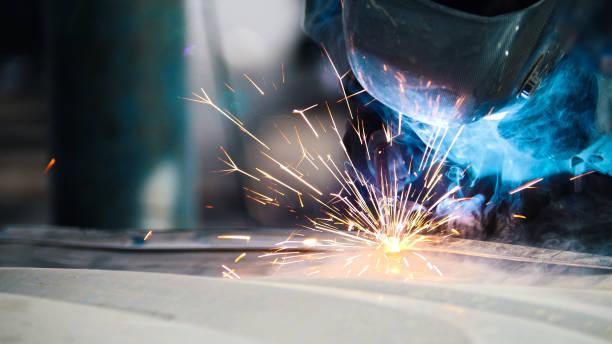 Industrial concept: worker in helmet repair detail in car auto stock photo