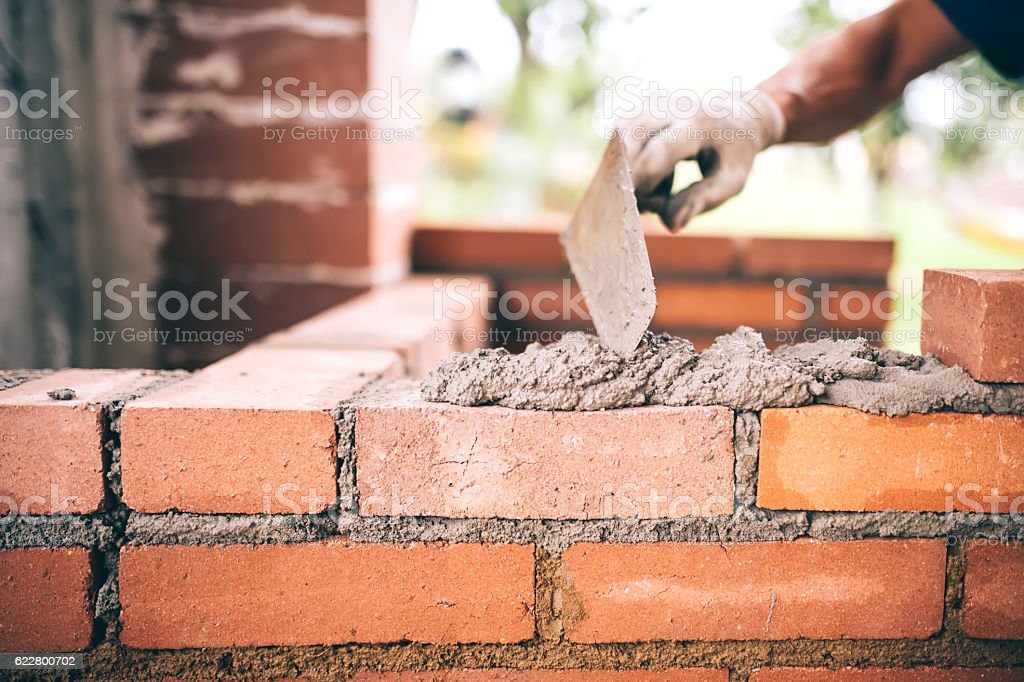 industrial Construction bricklayer worker building walls with bricks, mortar stock photo