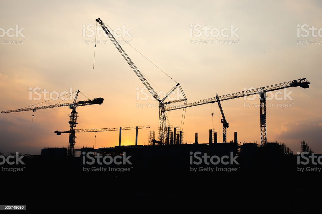 Industrial construction crane working and building stock photo