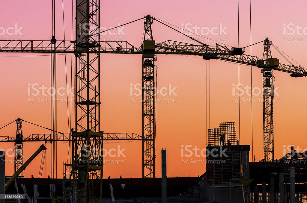 Industrial construction cranes and building silhouettes over sun at sunset stock photo