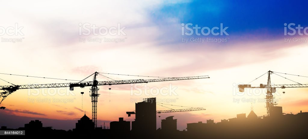 Industrial construction cranes and building silhouettes over sun at sunrise. stock photo