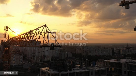 Industrial construction cranes and building silhouettes over sunset background and sunrise. aerial photography