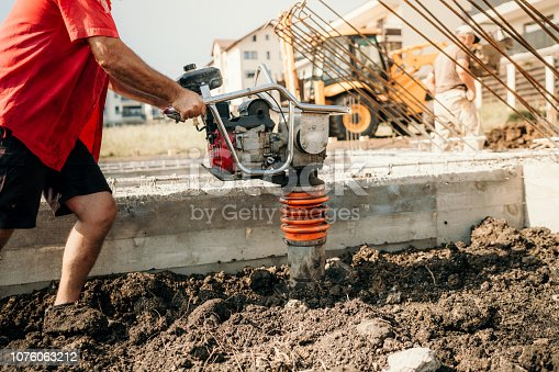 Industrial construction worker compacting soil with vibration compaction machine