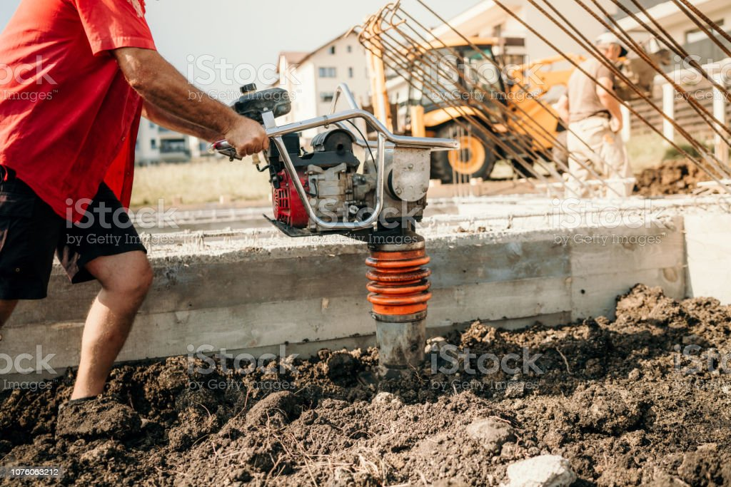 Industrial construction worker compacting soil with vibration compaction machine stock photo