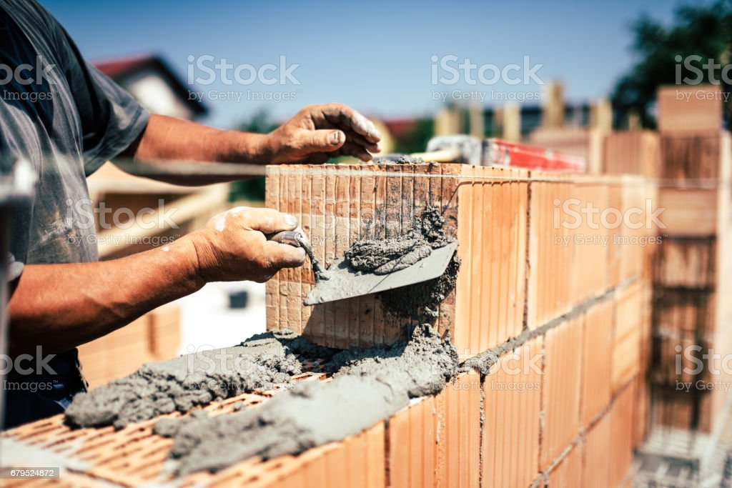 Industrial construction worker using spatula and trowel for building walls with bricks and mortar stock photo
