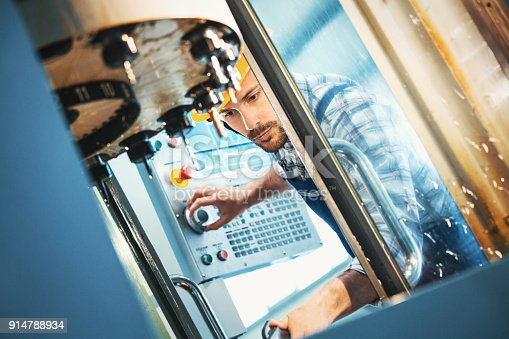 Closeup low angle view of a control room at a modern industrial production line with a control person in charge keeping track of the process on a computer. Employee is operating a CNC machine.