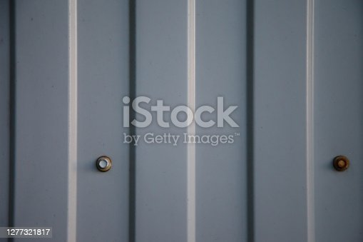 Industrial corrugated iron industrial texture wall made of tin sheets with bolts. Grunge metal plate background. Copyright space for site