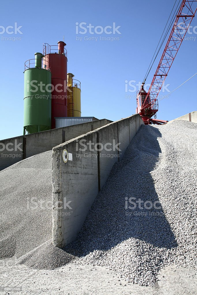 Industrial crane and three colorful storage tanks royalty-free stock photo
