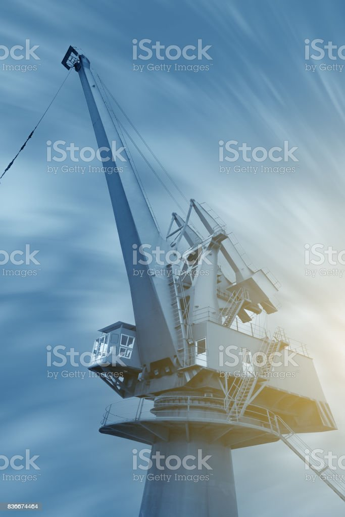 Industrial Crane operating and lifting an electric generator against sunlight and blue sky stock photo