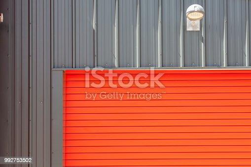 Industrial design. Bright red metal warehouse building roller shutter door. Garage style rolling door with confident contemporary modern paintwork.