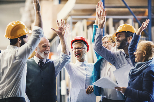 Closeup side view of mixed age people of industrial design department at a factory. They are gathered at a desk and celebrating successful job by giving a high five.