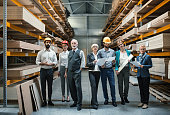 Closeup front view of mixed age people of industrial design department at a factory. They are standing in an aisle between pallet racks stacked with chipboard, MDF and plywood. There are three men and three women.