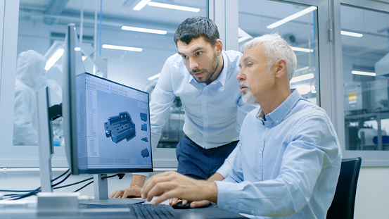 Industrial Designer Has Conversation With Senior Engineer While Working In Cad Program Designing New Component He Works On Personal Computer With Two Monitors Stock Photo - Download Image Now
