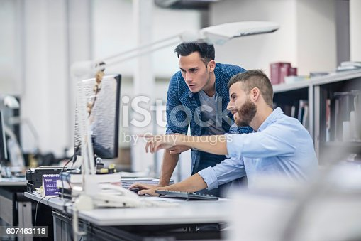 istock Industrial designers at the office discussing project on the computer 607463118
