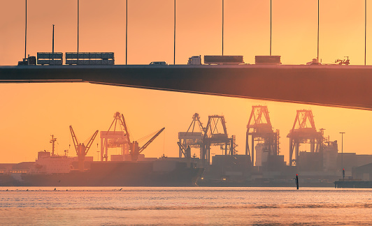 A road bridge with trucks, cars and a fork lift truck is in silhouette over an industrial docklands skyline at dusk on the Yarra river, Melbourne