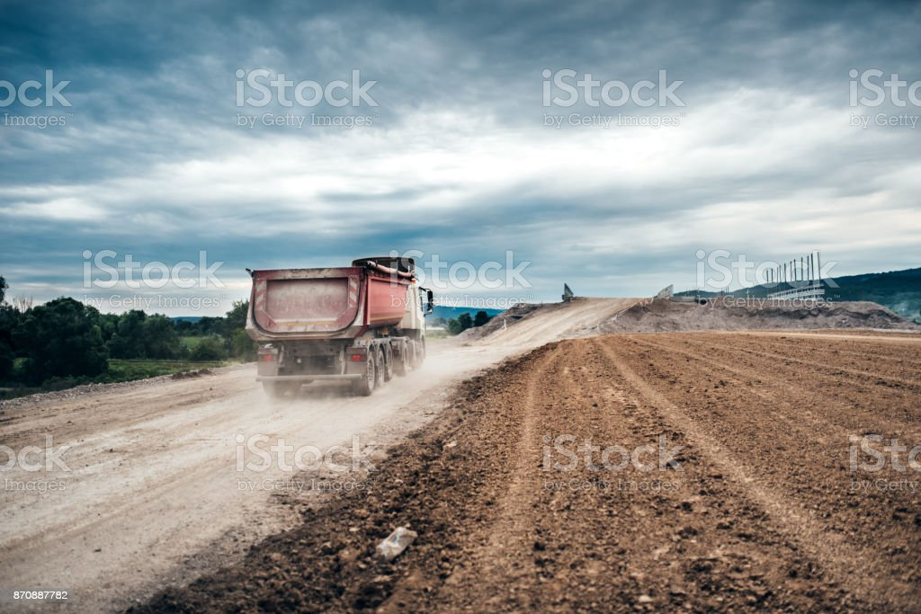 Industrial dumper trucks working on highway construction site, loading and unloading gravel and earth. stock photo
