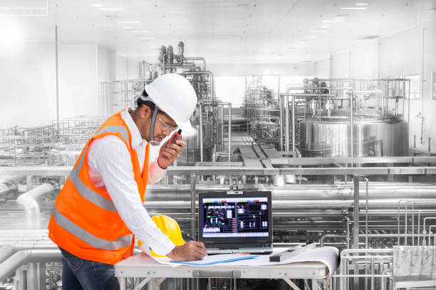 Industrial engineer checking machine status with computer stock photo