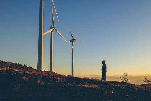 Industrial engineer in a windfarm, at sunset.