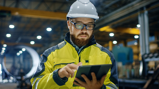 istock Industrial Engineer in Hard Hat Wearing Safety Jacket Uses Touchscreen Tablet Computer. He Works at the Heavy Industry Manufacturing Factory. 879814122