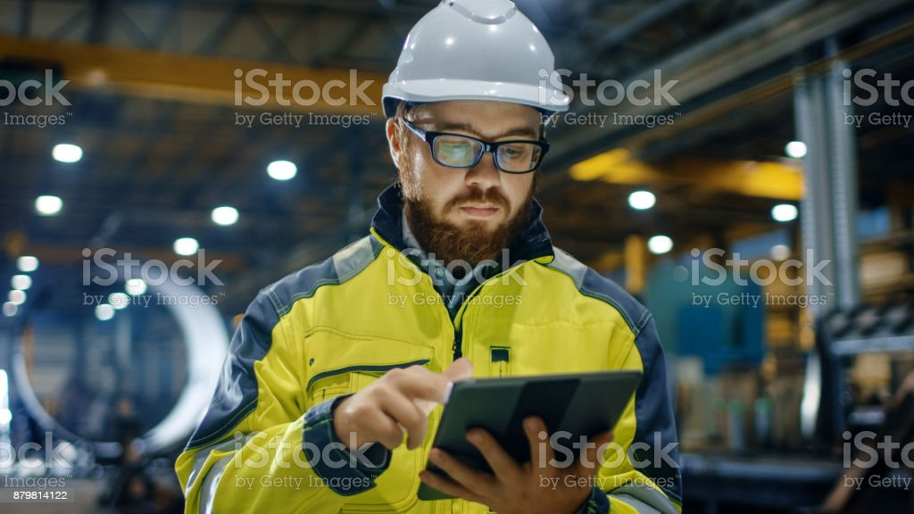 Industrial Engineer in Hard Hat Wearing Safety Jacket Uses Touchscreen Tablet Computer. He Works at the Heavy Industry Manufacturing Factory. stock photo
