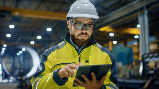 industrial engineer in hard hat wearing safety jacket uses touchscreen tablet computer. he works at the heavy industry manufacturing factory. - ingegneria foto e immagini stock