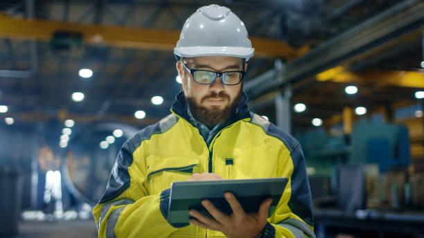 Ingeniero industrial en casco, con chaqueta de seguridad utiliza pantalla táctil Tablet PC. Trabaja en la industria pesada fábrica. - foto de stock
