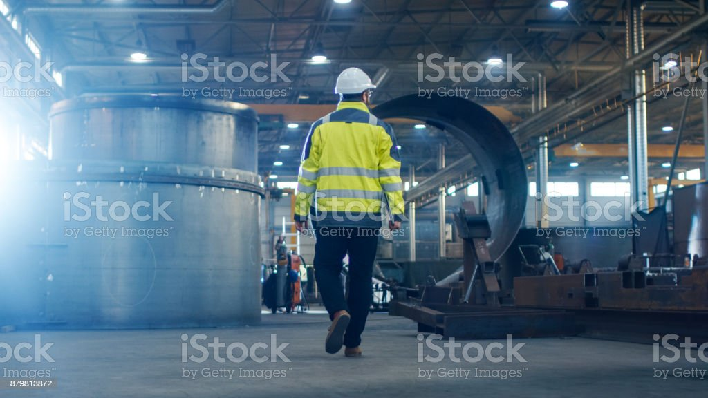 Industrial Engineer in Hard Hat Wearing Safety Jacket Walks Through Heavy Industry Manufacturing Factory with Various Metalworking Processes. Industrial Engineer in Hard Hat Wearing Safety Jacket Walks Through Heavy Industry Manufacturing Factory with Various Metalworking Processes. Built Structure Stock Photo