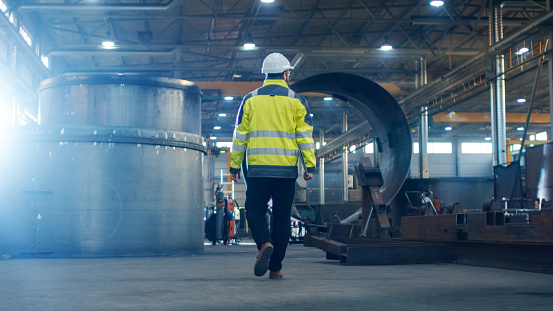 Industrial Engineer In Hard Hat Wearing Safety Jacket Walks Through Heavy Industry Manufacturing Factory With Various Metalworking Processes Stock Photo - Download Image Now