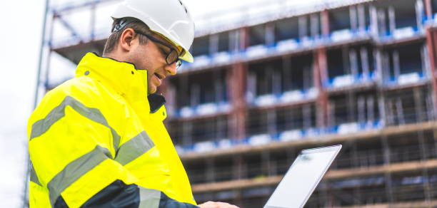 Industrial Engineer using laptop. Architect insect site with the drawings and laptop. digital drawings checked on site. Metalworking and construction industry. Construction worker using laptop on site. Construction worker with building plans and cellphone stock photo
