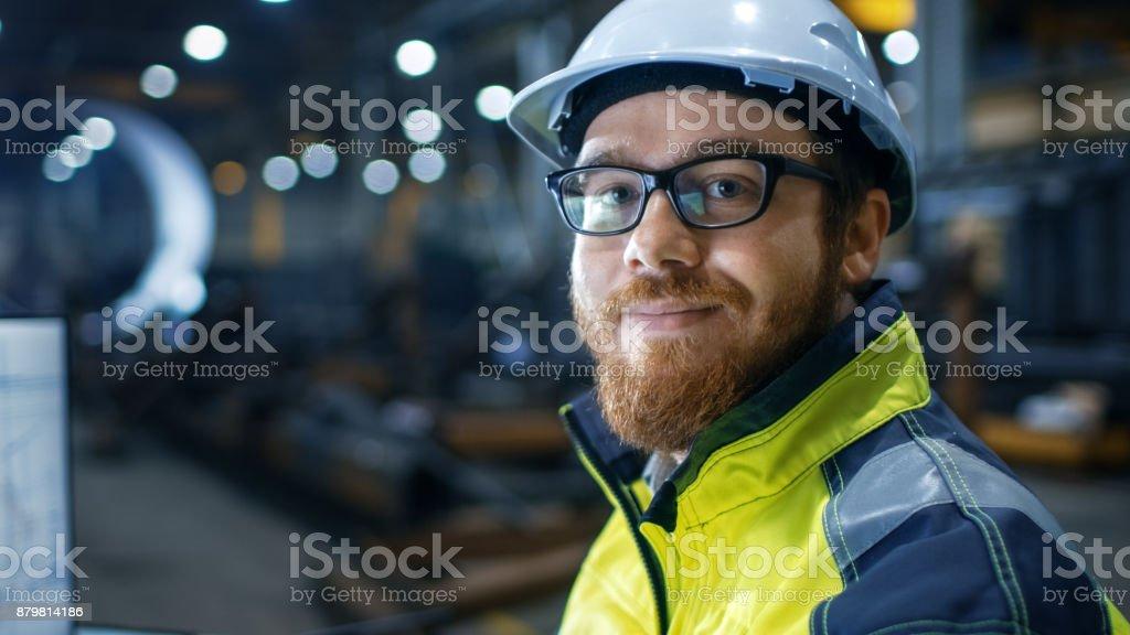 Wirtschaftsingenieur tragen Schutzhelm, Sicherheitsweste und Gläser Lächeln vor der Kamera. Er arbeitet in großen Schwerindustrie Fabrik. – Foto