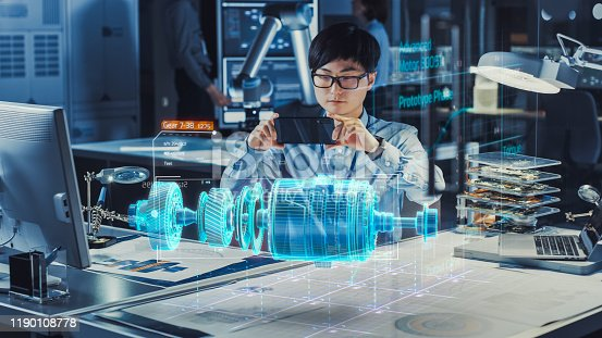 1150202727 istock photo Industrial Engineer Works with Smartphone Using Augmented Reality Holographic Projection 3D Model of the Electric Generator Prototype. Development of Virtual Mixed Reality Application. 1190108778
