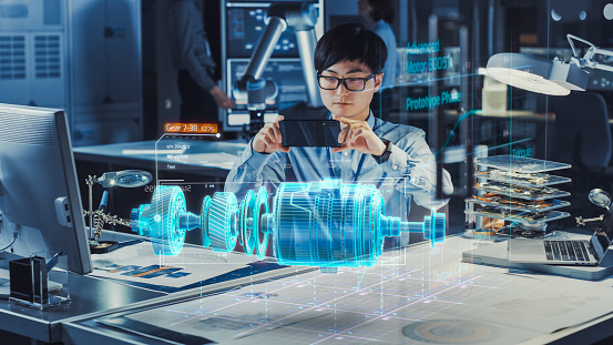 Industrial Engineer Works with Smartphone Using Augmented Reality Holographic Projection 3D Model of the Electric Generator Prototype. Development of Virtual Mixed Reality Application.