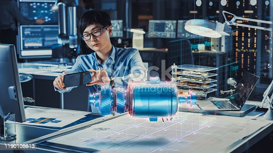 1150202727 istock photo Industrial Engineer Works with Smartphone Using Augmented Reality Holographic Projection 3D Model of the Electric Generator Prototype. Development of Virtual Mixed Reality Application. 1190108813