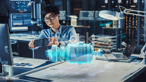1150202727 istock photo Industrial Engineer Works with Smartphone Using Augmented Reality Holographic Projection 3D Model of the Enlectric Motor Prototype. Development of Virtual Mixed Reality Application. 1190108824