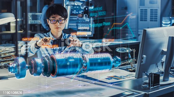 1150202727 istock photo Industrial Engineer Works with Smartphone Using Augmented Reality Holographic Projection 3D Model of the Electric Motor Prototype. Development of Virtual Mixed Reality Application. 1190108826