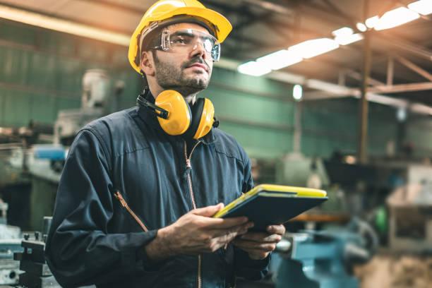 inżynierowie przemysłowi w hard hats.work w fabryce przemysłu ciężkiego. człowieka pracującego w fabryce przemysłowej. koncepcja bezpieczeństwa. - kask ochronny odzież ochronna zdjęcia i obrazy z banku zdjęć