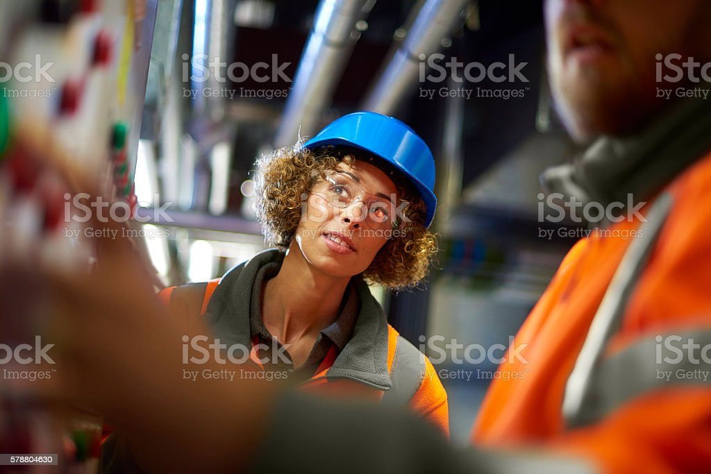 two industrial service engineers conduct a safety check of a control...