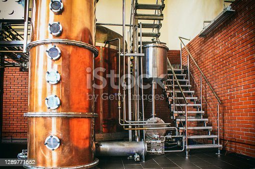 istock Industrial equipment for brandy production. Copper still alembic inside distiller to distill grapes and produce spirits. Noises and large grain - stylization under the film. Soft focus 1289771552